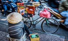 2019 - Vietnam - Ho Chi Minh City - 50 - Streetside Vendor (Ted's photos - Returns Early February) Tags: 2019 cropped hochiminhcity nikon nikond750 nikonfx saigon tedmcgrath tedsphotos vietnam vignetting conical conicalhat nónlá streetscene street motorcycles busystreet hcmc bicycle scale weighscale hat sidewalk pedals wheels bike blur