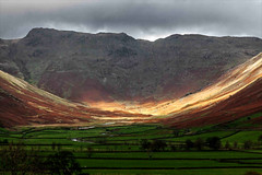 On a stormy day a shaft of sunlight lights up the Langdale Valley (Iand49) Tags: langdalevalley langdale ambleside lakedistrict england europe autumn november stormy shafts sunlight dramatic nature outdoor ruggedterrain darkclouds autumnalcolours goldenbracken river stream beck fields greengrass mountains crags fells trees landscape picturesque moody atmospheric majesticmountains scenery scenicview tourism travel holidays fellwalking rambling hiking rural remote