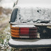 Old rusty Mecedes W112 in the snow. Back view closeup.