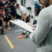 close up view of trainer writing in notebook while men working out in gym.