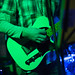 Guitar player playing an electric guitar on stage. Closeup.