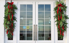 Closed till next year (*Millie*) Tags: doors decoration christmas ribbons pinecones red green pine reflection glass white canoneos5dmarkiii milliecruz ef50mmf18stm holiday season swag