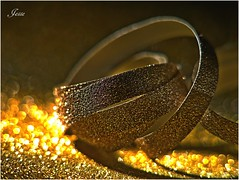 Discarded (jesse1dog) Tags: ribbon discarded wrappingpaper bokeh vintageprime pentaxauto11070mm 70mm tabletop sparkle gold burninggold panasoniclumixgm1 lookingcloseonfriday ribbons