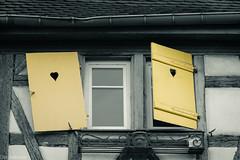 Etwas schräg --- Somewhat crooked (der Sekretär) Tags: alsace colmar dach dachrinne dachziegel detail eisen elsass fachwerk fassade fenster fensterglas fensterrahmen fensterscheibe france frankreich gebäude glas haus herz holz metall putz regenrinne scheibe schmiedeeisen abgeblättert abgebröckelt alt askew bend bent bröcklig building closeup crooked facade façade front geschmiedet glass gutter halftimbered halftimbering halftimer heart house iron krumm krummundschief metal old pane rendering roof rooftiles schief tiles truss verbiegen verbogen verwittert weatherbeaten weathered window windowframe windows wood wroughtiron fensterladen windowshutter