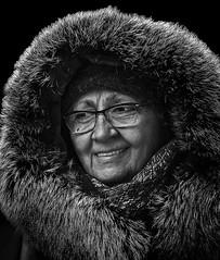 Portrait (D80_548930) (Itzick) Tags: candid copenhagen bw winterportrait hoodie woman face facialexpression streetphotography smile fur blackbackground glasess portrait denmark d800 itzick