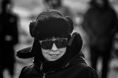 A lady who knows her ABCs (Frank Fullard) Tags: frankfullard fullard candid street portrait alphabet lady shades fur fauxfur hat cool warm achill mayo newyearsday dugort irish ireland black white blanc noir monochrome smile enigmatic mysterious