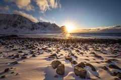 Snowy Beach (Hilton Chen) Tags: archipelago arctic landscape leadinglines lofoten lofotenislands norway rocky snow sunburst sunset sunstar surfing unstadbeach winter