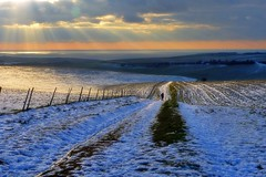 Figure on the path ((Sue Lockhart Images)) Tags: sunset crepuscularrays weather clouds snow path fence figure cliffs sea sky