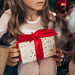 Young girl holding beautiful Christmas gift. Closeup