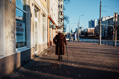 Burdens (ewitsoe) Tags: 35mm everydaymoments nikon street warszawa winter citylife erikwitsoe poland urban warsaw woman shadow walking cane furcoat sunny morning elderly