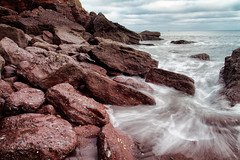 Red Rocks at Maidencombe (Christian Hacker) Tags: maidencombe torquay seascape longexposure cokin nd8filter redrocks redcliffs cliffface water watermovement barnacles southdevon sea atlantic overcast landscape canon eos50d tamron 1750mm outdoors nature wet tide wave redsand sandybeach coast coastal boulders geology erosion