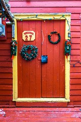 Old Christmas Day (Karen_Chappell) Tags: door red paint wood wooden painted christmas xmas noel holiday nfld stjohns architecture shed building house trim clapboard wreath green number yellow thebattery canada eastcoast atlanticcanada avalonpeninsula colour color colors colours colourful canonef24105mmf4lisusm