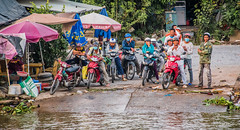 2019 - Vietnam-Avalon Siem Reap - 17 - River Cruise - Mekong River Ferry Dock (Ted's photos - Returns Early February) Tags: 2019 avalonwaterways cropped mekongriver nikon nikond750 nikonfx tedmcgrath tedsphotos vietnam vignetting motorcycles people groupphoto group smiles helmut helmuts rivershore ferrylanding mekongriverferrylanding umbrellas wheels