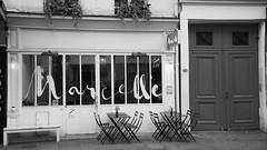 Marcelle (Titole) Tags: restaurant noirblanc titole nicolefaton bw blackwhite nb letters marcelle door chair table bench white ruemontmartre paris