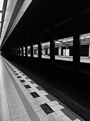 Schiphol Airport. I like the repeating lines. (kev_zilla) Tags: blackandwhite trains platform lines station architecture manmade travel train holland schiphol