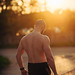Musculine man posing at sunset on street
