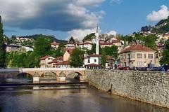 Latina Bridge, Sarajevo (Jocelyn777) Tags: architecture buildings bridges rivers water cityscapes landscapes cityviews mountains trees foliage reflections citycentre balkans bosniaandherzegovina sarajevo travel sky clouds
