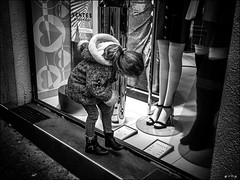 N'a-t-elle pas froid aux pieds?  /   Are'nt her feet cold? (vedebe) Tags: rue street city ville urbain urban magasins pieds noiretblanc netb nb bw monochrome enfant