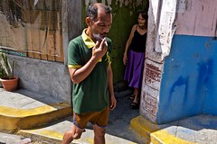 Ships Passing (Rick Del Carmen) Tags: philippines manila color alley sidewalk woman man cigarrette smoke smoking streetphotography colorstreetphotography