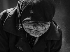 Unhappiness (Ales Dusa) Tags: woman unhappiness beggar poor powerty homeless oldwoman elderly closeupportrait outdoor street candid portrait face alesdusa dramaticshot monochrome headscarf wrinkles blackandwhite bw overcoat texture streetportrait canon