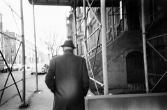 Man in Gabardine (Gabriella Ollandini) Tags: man streetphotography urban city nyc newyork 35mm filmisnotdead analog filmnoir bw monochrome winter vintage 1930 1940 fifties forties thirties lomography hat cinematic istillshootfilm analogue