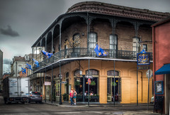 Pere Antoine Restaurant (donnieking1811) Tags: louisiana neworleans pereantoinerestaurant restaurant architecture building wroughtiron railing balcony people signs automobiles streets flags outdoors exterior sky clouds hdr canon 60d lightroom photomatixpro
