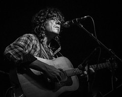 Acoustic (tim.perdue) Tags: acoustic guitar singer vocalist musical instrument band music concert performance live stage rumba cafe ohio columbus black white bw monochrome blackandwhite mono nikon z50 z 50 nikkor 1650mm man person figure musician jazz rock pop morphine cure for pain tribute show bar club nightclub candid light dark shadow microphone mic curly hair plaid shirt