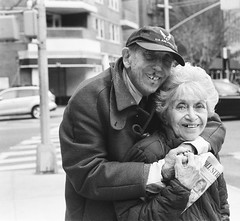 Young Love (Gabriella Ollandini) Tags: portrait people streetphotography 35mm love senior analog togetherness candid couple humans nyc city brooklyn bw monochrome filmisnotdead filmphotography age pensioner ricoh hug smiling pair partner husband wife affection hp5 ilford hat cap happy analogue old retiree mature married