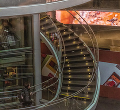 Man Walking Up Winding Stairway In Fulton Center Transportation Hub (nrhodesphotos(the_eye_of_the_moment)) Tags: dsc39693001920 wwwflickrcomphotostheeyeofthemoment theeyeofthemoment21gmailcom fultoncenter transportationhub stairway curve perspective neonsign metal glass indoors man elevator display lights manhattan nyc winding season wintertime reflections shadows