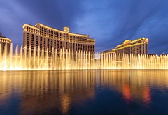 The Bellagio Fountains (Karen_Chappell) Tags: lasvegas travel fisheye canonef815mmf4lfisheyeusm wideangle architecture night longexposure water fountain hotel building landscape city urban usa nevada cityscape yellow gold golden lights sky blue