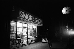 Smoke Shop (Gabriella Ollandini) Tags: shopfront store storefront retro night filmisnotdead filmphotography nyc brooklyn city urban illuminated 35mm filmcamera street streetphotography filmnoir bw monochrome lomography grain softfocus cigarette neon cinematic
