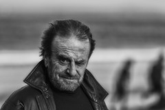 Watching me (Frank Fullard) Tags: frankfullard fullard candid street portrait watching eye seeing beard hair windswept achill mayo dugort doogort irish ireland rnli lifeboat black white blanc noir monochrome beach seaside fundraiser newyear swim