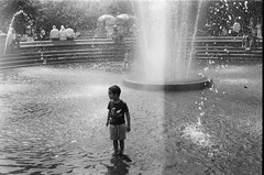 Washington Square Park, Manhattan, NYC (Gabriella Ollandini) Tags: boy child play fun fountain water summer heat hazy 35mm film photography grain monochrome helios istillshootfilm filmisnotdead nyc manhattan analog analogue silhouette splash lightleak kids children analogica city urban