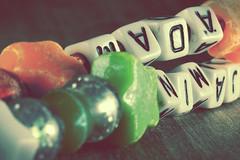the importance of names (kerwitcherwoo) Tags: smileonsaturday beads keyrings names letters green orange vintage macro bokeh stars creativetabletopphotography light shade cubes squares