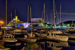 Imposing! (Fnikos) Tags: port puerto harbor sea mar mare water serene waterfront sky cielo ship boat building architecture construction color colour colores colours colors blue blau azul blu pink rosa light lights reflections shadow shadows dark darkness barceloneta barcelona night nightview nightshot pentax outside outdoor