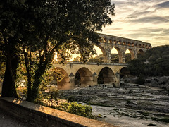 Pond du Gard Sunset (Explored) (Katrina Wright) Tags: 2019 france iphone6 pontdugard aqueduct img2232iphone6 goldenlight arches line pattern sturdy structure architecture light