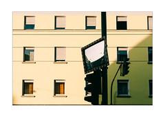 Hiding (Thomas Listl) Tags: thomaslistl color urban 50mm mirror windows facade sunlight sunny trafficlight trafficsigns yellow green bright contrast urbanlife geometric architectural