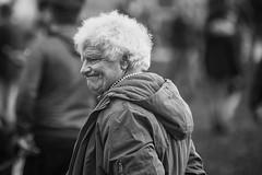 Wry smile (Frank Fullard) Tags: frankfullard fullard candid street portrait wry smile parka white hair curls black blanc noir monochrome horse fair ballinasloe galway irish ireland face expression outdoor