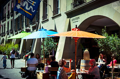 Umbrellas (dlerps) Tags: amount bern ch che city daniellerps eu europa europe lerps photography schweiz sony sonyalpha sonyalpha99ii sonyalphaa99mark2 sonyalphaa99ii summer swiss switzerland urban httplerpsphotography lerpsphotography umbrella shade cafe coffeehouse restaurant streetphotography carlzeiss planar5014za planart1450 colours blue orange drinking carlzeissplanar50mmf14ssm