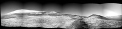 The Center of Gale Crater (sjrankin) Tags: 13january2020 edited nasa mars msl curiosity galecrater panorama mountains mountsharp craterrim sky haze rocks sand dust grayscale