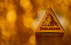The Golden Triangle... (Aleem Yousaf) Tags: nikon d850 nikkor105mm bokeh macro closeup shallow depth field tabletop light studiophotography creative flickr macromondays triangle chocolate bar brand golden colours abundance red candle lit tealight swiss mondelez international kraft foods jacobs suchard bern logo distinctive prism