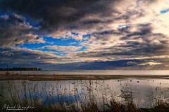 The Barrier (Alfred Grupstra) Tags: nature cloudsky sky water landscape lake reflection outdoors scenics cloudscape sunset blue summer marsh sea beach beautyinnature coastline river tranquilscene