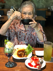 An old Chinese woman enjoys eating in Japanese restaurant, using chopsticks. (baddoguy) Tags: 7079 years 8089 active seniors adult adults only asian indian ethnicities bowl cheerful chinese culture chopsticks color image cup dessert topping dining table dinner drinking glass eating enjoyment females fine food drink front view frozen gourmet happiness holding ice cream joy leisure activity lifestyles lunch meal one person senior woman women people photography positive emotion recreational pursuit restaurant retirement sitting skill smiling sweet thailand vertical waist up wood material