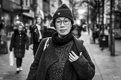 Woolly Jumper (Leanne Boulton) Tags: urban street candid portrait portraiture streetphotography candidstreetphotography candidportrait streetportrait eyecontact candideyecontact streetlife woman female face eyes expression mood emotion feeling glasses beanie hat woolly jumper sweater cold winter weather tone texture detail depthoffield bokeh naturallight outdoor light shade city scene human life living humanity society culture lifestyle people canon canon5dmkiii 70mm ef2470mmf28liiusm black white blackwhite bw mono blackandwhite monochrome glasgow scotland uk