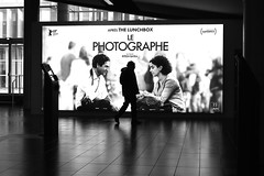 In front of the photographer (pascalcolin1) Tags: paris13 homme man photographe photographer cinema affiche poster reflets reflection lumière light mur wall photoderue streetview urbanarte noiretblanc blackandwhite photopascalcolin 50mm canon50mm canon