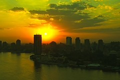 Cairo and Nile at Sunset (Herculeus.) Tags: city water river outside outdoors outdoor egypt dec 2010 nileriver sunset sun buildings evening landscapes smog haze cityscape hirise