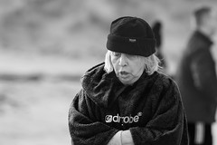 Freezing ... for a good cause (Frank Fullard) Tags: frankfullard fullard candid street portrait freezing frozen cold swim charity fundraiser achill island rnli lifeboat mayo irish ireland black white blanc noir monochrome bathrobe cap blonde lady goodcause help