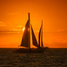 Silhouette of sailboat in front of setting sun at Fort Zachary Taylor State Park, Key West, Florida