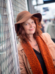 Hanneke, Amsterdam 2019: Leaning on the fence (mdiepraam) Tags: hanneke amsterdam 2019 amsterdamcentraal station pretty attractive beautiful elegant classy gorgeous dutch redhead woman lady naturalglamour curls coat mature milf hat scarf architecture portrait