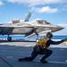 Sailors signal an F-35B Lightning II to take off from flight deck of amphibious assault ship USS America